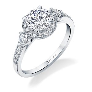 A white gold three stone diamond engagement ring with a halo around the center diamond from the Sylvie Collection