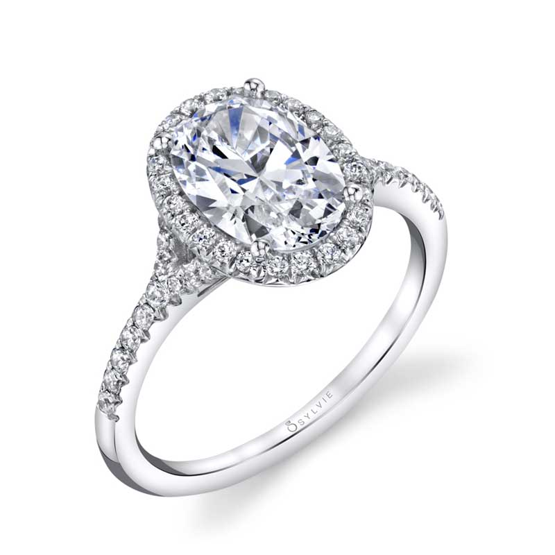 A white gold diamond engagement ring from the Sylvie Collection with an oval cut diamond in the middle of a halo mounting