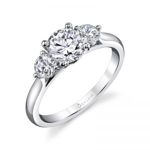A white gold diamond engagement ring from the Sylvie Collection featuring a large round diamond with a slightly smaller round diamond on either side