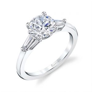 A white gold three stone diamond engagement ring from the Sylvie Collection featuring a large round diamond in the center with two baguette cut diamonds on the side