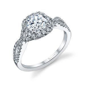 A white gold diamond engagement ring from the Sylvie Collection highlighted by a twisting diamond shank and a cushion shaped halo around a round diamond