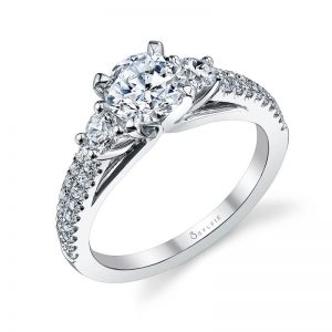 A while gold three-stone diamond engagement ring from the Sylvie Collection featuring three diamonds at the top as well as two rows of diamonds going down either side