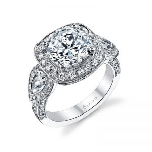 A white gold halo accented three stone style engagement ring with from the Sylvie Collection