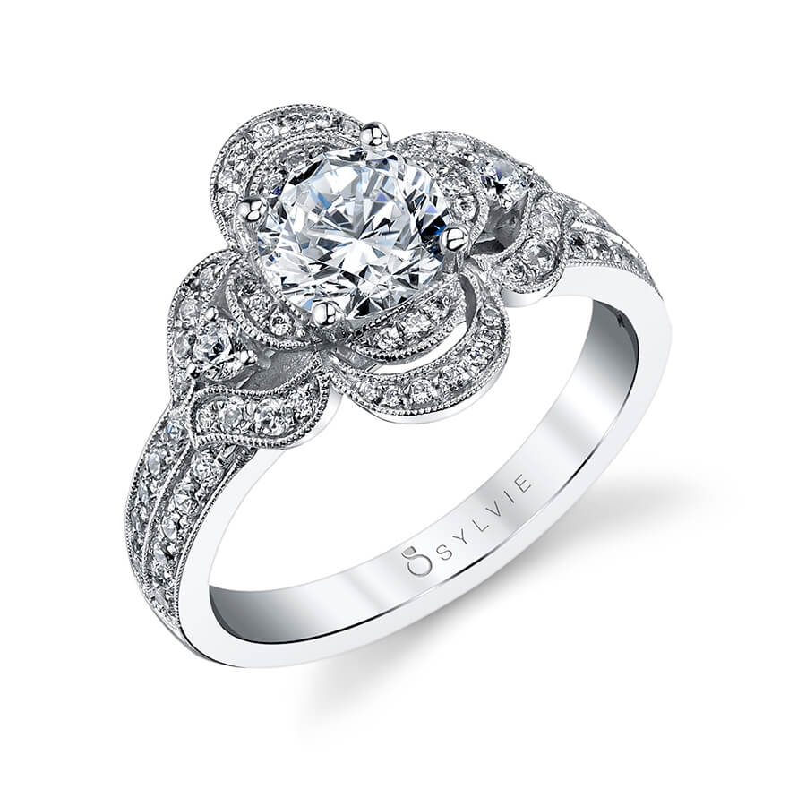 "A floral themed white gold diamond engagement ring from the Sylvie Collection with ""petals"" set with diamonds around a round diamond"