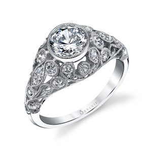 A vintage style white gold diamond engagement ring from the Sylvie Collection featuring a large bezel set diamond and milgrain accented swirling patterns