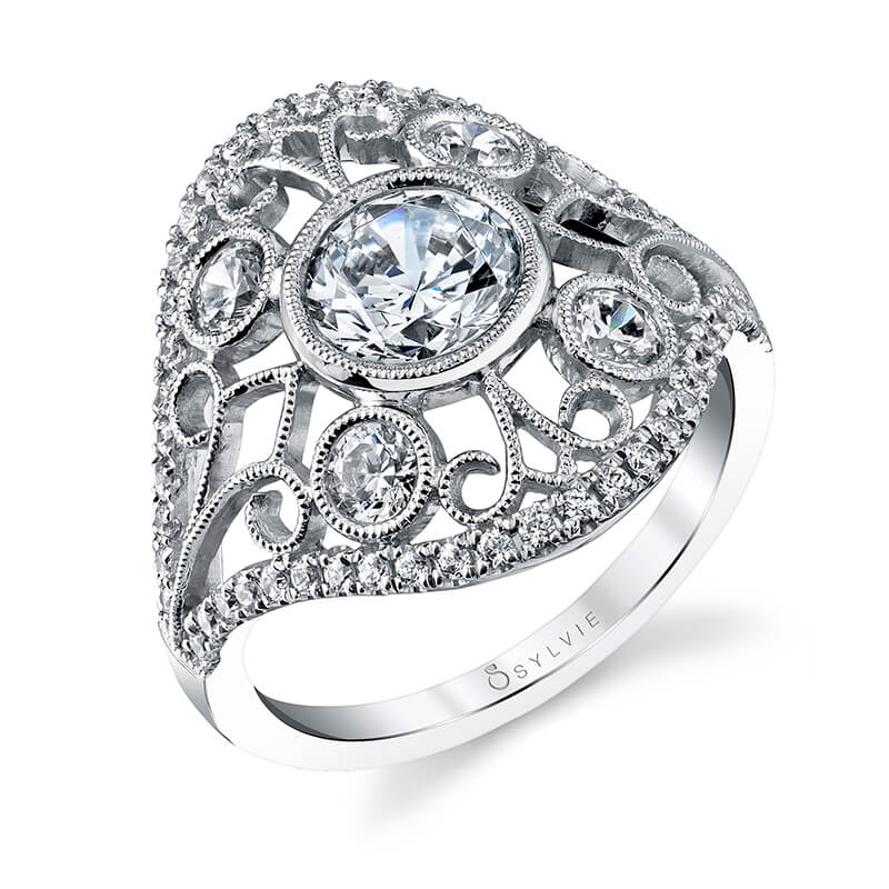 A white gold diamond ring from the Sylvie Collection with a diamond edge and bezel set diamonds among a swirling design