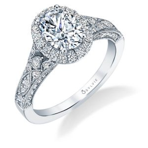 A white gold diamond engagement ring from the Sylvie Collection featuring an oval shaped diamond in the center of a halo mounting with milgrain accents and an art deco style