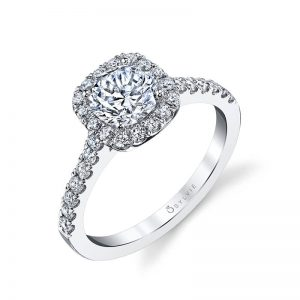 A white gold diamond engagement ring from the Sylvie Collection features a round diamond in the center with a cushion shaped halo around it