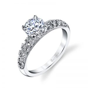 A white gold diamond engagement ring from the Sylvie Colleciton featuring diamond accented swirls and a large prong set diamond