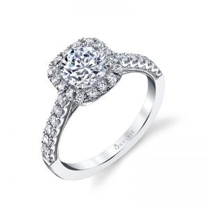 A white gold diamond engagement ring from the Sylvie Collection featuring a prominent round diamond in the middle of a cushion shaped halo