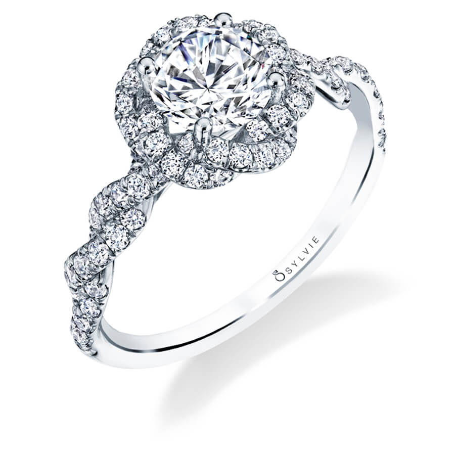 A white gold diamond engagement ring from the Sylvie Collection featuring a twisting diamond halo and shank