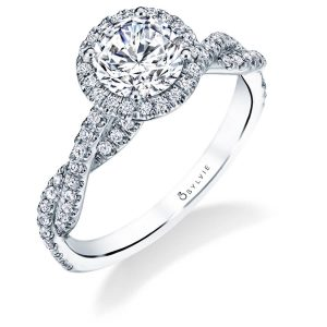 A white gold diamond engagement ring from the Sylvie Collection featuring a twisting diamond shank accompanying a round diamond halo