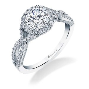 A white gold diamond engagement ring from the Sylvie Collection featuring a round diamond surrounded by a halo setting and a twisting shank