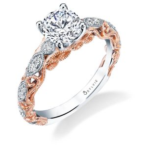 Prominent rose gold swirls adorn the side of a white gold diamond studded white gold two-tone engagement ring from the Sylvie Colection