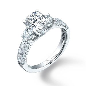 A white gold three stone diamond engagement ring with a peek-a-boo diamond on the side from the Sylvie Collection