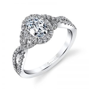 A white gold diamond engagement ring from the Sylvie Collection featuring an oval shaped diamond in the middle with an corresponding halo and a twisting diamond shank
