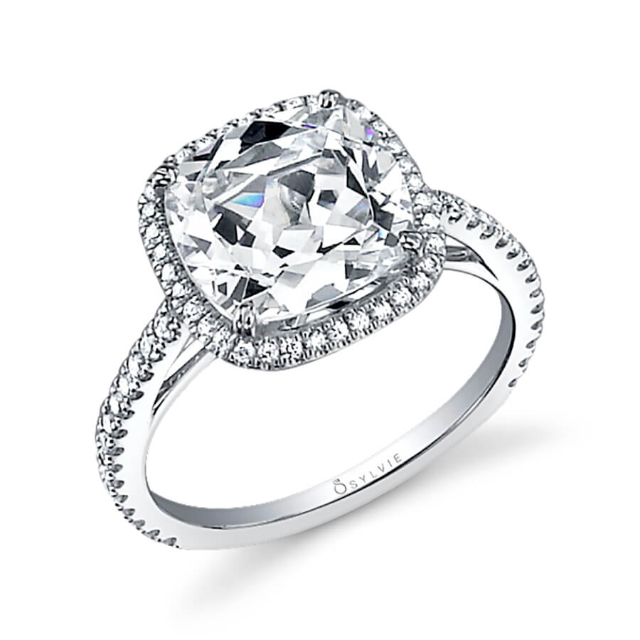 A white gold diamond engagement ring from the Sylvie Collection featuring a large cushion cut diamond in the center with a simple halo mounting around it
