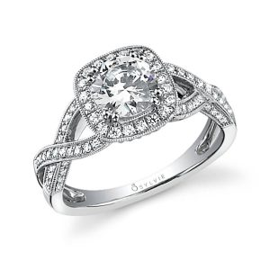 A white gold diamond engagement ring featuring a cushion shaped halo around a round diamond with milgrain accents