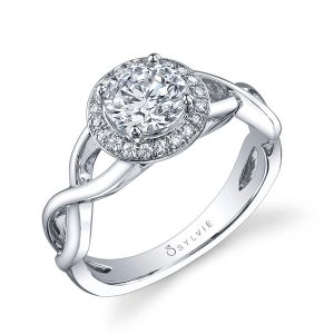 A white gold diamond engagement ring from the Sylvie Collection featuring a plain twisting shank and a round diamond inside of a halo mounting