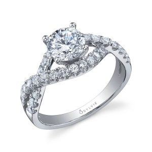 A white gold diamond engagement ring from the Sylvie Collection featuring a twisting diamond shank and prominent round diamond in the center