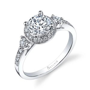 A white gold three-stone diamond ring with a halo around the center stone from the Sylvie Collection