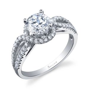 A white gold diamond engagement ring from the Sylvie Collection featuring a round center diamond and a twisting shank with diamonds