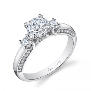 A white gold diamond engagement ring from the Sylvie Collection featuring a three-stone design with diamonds set in the side of the ring
