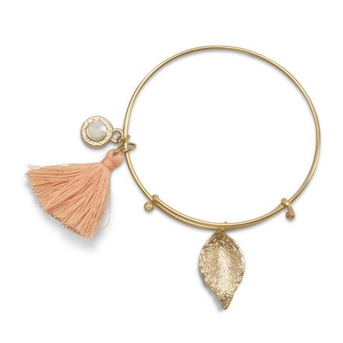 Gold tone fashion bangle with peach tassel and gold tone charm